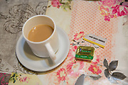 A cup of tea placed a floral plastic table lining at the Farm Cafe in rural Holbeach on the 23rd June 2017 in Norfolk, United Kingdom. Established during the 1950's after the owners parents set up a tea stop on the east bound A17, the cafe has grown over the years and attracts coach loads of tourist and travellers often en route to the north Norfolk coast.