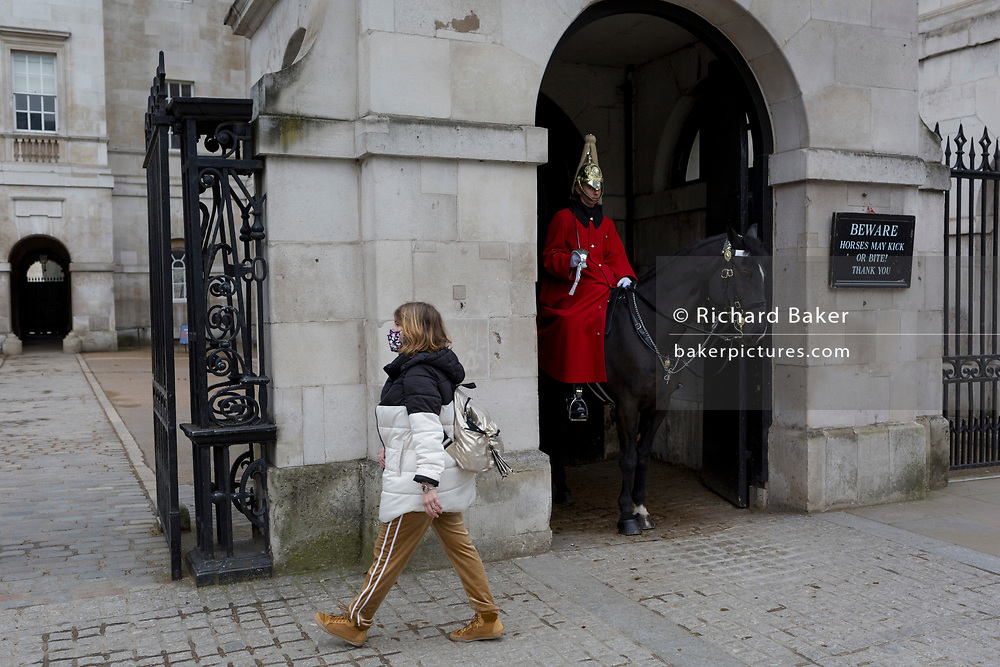 As the Coronavirus pandemic spreads across the UK, businesses and entertainment venues not already closed with the threat of job losses, struggle to stay open with growing rumours of a lockdown and travel restrictions around the capital. As Londoners start to work from home, a masked lady walks past an otherwise deserted Horseguards Parade, usually crowded by tourists at this famous London landmark, on 19th March 2020, in London, England.