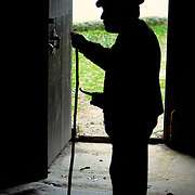 Man standing by a door of a palloza, a traditional straw house at Spain's Ancares mountains
