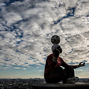 FRANCE. Paris, Ile-de-France. December 8th, 2014. Athlete Iya Traoré, performs a dance with a soccer ball in Montmartre at sunset.
