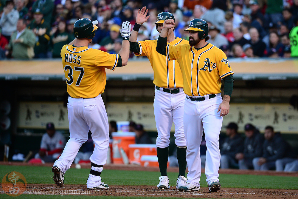 July 2, 2012; Oakland, CA, USA; Oakland Athletics first baseman Brandon Moss (37) is congratulated by left fielder Seth Smith (center) and catcher Derek Norris (right) after hitting a three-run home run during the second inning against the Boston Red Sox at O.co Coliseum.