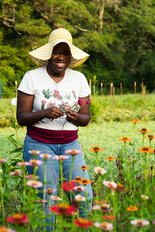 Young smiling woman cuts flowers in a flower field in Atlanta, Georgia.