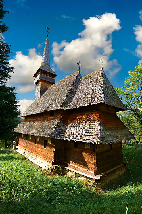 Wood Church of  the orthodox  Cuvioasa Paraschiva , Poienile Izei, Maramures, Northern Transylvania, Romania. Romania. UNESCO World Heritage Site.  The Church of the Holy Parasceve (Poienile Izei) is one of the oldest of the wooden churches of Maramureş (1604), and reveals two phases in the development of such buildings. The first can be seen in the lower part of the walls with a sanctuary based on a square plan, a typical feature of the oldest wooden buildings. In the 18th century, the walls were raised, the naos was covered by a semi-circular vault, and the interior was decorated with paintings. The portico was added during the first half of the 19th century. .<br /> <br /> Visit our ROMANIA HISTORIC PLACXES PHOTO COLLECTIONS for more photos to download or buy as wall art prints https://funkystock.photoshelter.com/gallery-collection/Pictures-Images-of-Romania-Photos-of-Romanian-Historic-Landmark-Sites/C00001TITiQwAdS8<br /> .<br /> Visit our MEDIEVAL PHOTO COLLECTIONS for more   photos  to download or buy as prints https://funkystock.photoshelter.com/gallery-collection/Medieval-Middle-Ages-Historic-Places-Arcaeological-Sites-Pictures-Images-of/C0000B5ZA54_WD0s