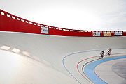 SHOT 7/27/14 6:40:23 PM - Jim Kinsinger (left) of Erie, Co. and Richard Godesiabois of Boulder, Co. take laps around the Boulder Valley Velodrome track in Erie, Co. one recent weekend evening. The velodrome is the first of its kind in the Denver metro area and one of only some twenty or so in the United States. At 250 meters, the Erie track stretches longer than most velodromes but the distance has become the preferred track length for Olympic events. Pitched at 12 degrees on the straightaways and 42 degrees on the turns, the track mimics the one used during the 2012 London Olympics. The velodrome is co-owned by University Cycles founder Doug Emerson and his partner, Frank Banta. (Photo by Marc Piscotty / © 2014)
