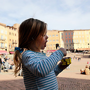 SIENA, ITALY - OCTOBER 28: A three year old girl eating a gelato in the Piazza del Campo in Siena, Italy. Siena is a city in central Italy's Tuscany region, is distinguished by its medieval brick buildings. The fan-shaped central square, Piazza del Campo, is the site of the Palazzo Pubblico, the Gothic town hall, and Torre del Mangia, a slender 14th-century tower with sweeping views from its distinctive white crown. Siena, Italy. 28th October 2017. Photo by Tim Clayton/Corbis via Getty Images)