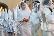 A young girl dressed in white carries a single rose during the Procession of Silence through the streets on Good Friday during Holy Week March 30, 2018 in Querétaro, Mexico. Hooded penitents, known as Nazarenes, and young girls symbolizing the Virgin Mary process through the streets of the city to recreate the passion of Christ.