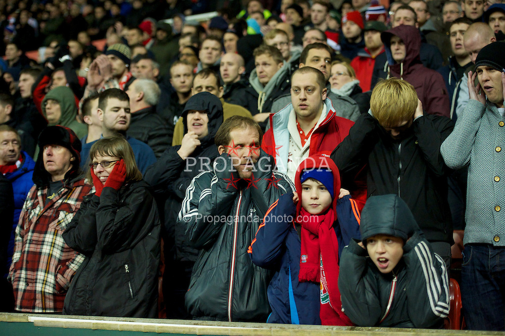 STOKE-ON-TRENT, ENGLAND - Boxing Day Wednesday, December 26, 2012: A Liverpool supporter cover their ears due to the incredibly loud speakers placed just in front of the travelling supporters during the Premiership match between Stoke City and Liverpool at the Britannia Stadium. (Pic by David Rawcliffe/Propaganda)
