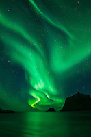 Northern Lights - Aurora Borealis shine in Sky over Vik Beach, Vestvågøy, Lofoten Islands, Norway