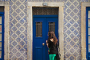 Lady opening the door of a house with a facade decorated with typical ceramic tiles facade at Madragoa district in Lisbon.
