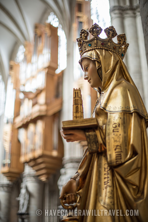 A statue of Saint Gudula, one of the cathedral's patron saints, at the Cathedral of St. Michael and St. Gudula (in French, Co-Cathédrale collégiale des Ss-Michel et Gudule). A church was founded on this site in the 11th century but the current building dates to the 13th to 15th centuries. The Roman Catholic cathedral is the venue for many state functions such as coronations, royal weddings, and state funerals. It has two patron saints, St Michael and St Gudula, both of whom are also the patron saints of Brussels.