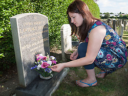 Young woman putting flowers on a grave