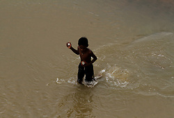 August 26, 2017 - Bhubaneswar, India - A rag picker holds a coconut and eats it after collecting from the river water inside the river Kuakhai as they are busy to collect reusable items from the festival rituals accessories throw by devotees into the water and sand bed of water bodies after finished the Ganesha Chatruthi festival int he eastern Indian state Odisha's capital city Bhubaneswar, on August 26, 2017. (Credit Image: © Str/NurPhoto via ZUMA Press)