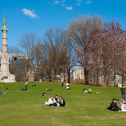 The Soldiers and Sailors Monument and people picknicking on the lawn in Boston Common park in spring