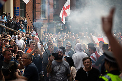© Licensed to London News Pictures. 01/06/2018. Leeds, UK. A smoke bomb is set off outside Leeds Crown Court . Supporters of EDL founder Tommy Robinson ( real name Stephen Yaxley-Lennon ) demonstrate in Leeds after Robinson was convicted of Contempt of Court . Robinson was already serving a suspended sentence for Contempt of Court over a similar incident , when he was convicted on Friday 25th May 2018 . Reporting restrictions , since lifted , initially prevented coverage of Robinson's arrest and incarceration . Photo credit: Joel Goodman/LNP