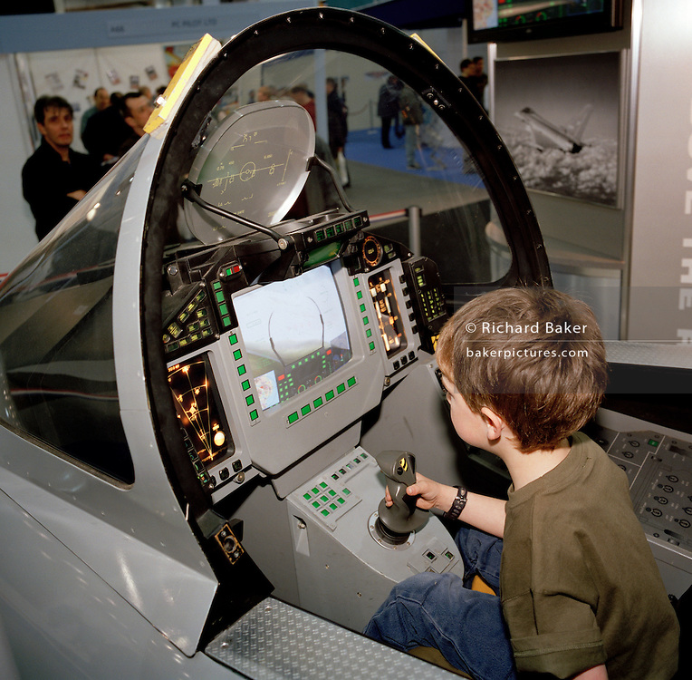 A young boy sits in BAE Systems Typhoon model cockpit.