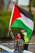 Birmingham, United Kingdom, June 14, 2021: A woman is seen waving a Palestinian flag outside the Arconic factory site in Birmingham after Palestine Action activists took over the rooftop of an American industrial factory known as Arconic in Birmingham on Monday, June 14, 2021. Some other activists used a sledgehammer to protest against the company who they say 'provided cladding for Grenfell Tower' and 'materials for Israel's fighter jets.' (Photo by Vudi Xhymshiti)