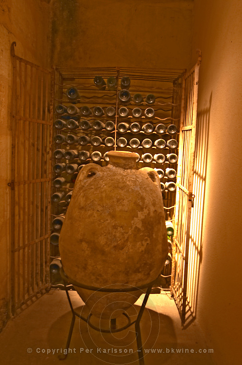 In a niche in the wine cellar ther is an old amphora and dusty old bottles of wine  Chateau Thieuley La Sauve Majeure  Entre-deux-Mers  Bordeaux Gironde Aquitaine France