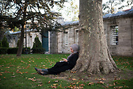 Tuğba, with a book and smartphone, sits on a beautiful autumn afternoon in the grounds of the Süleymaniye Mosque in Istanbul, Turkey. The mosque was built between 1550 and 1557.<br /> <br /> (Istanbul, Turkey - November 14, 2017)