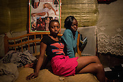 Sex workers Alice, 20 (L) and Claire 17, pose for a photograph as Alice's baby sleeps close by in their home in Kiamaiko, Nairobi, Kenya.