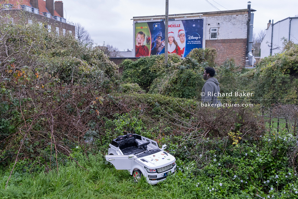 A discarded miniature child's toy car and nearby billboards ads promoting Disney Christmas films, in East Dulwich, on 25th December 2020, in London, England.