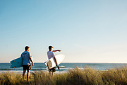 Two brothers standing in the sand dunes, holding surfboards, watching the surf and waves breaking at sunset  at St Ouen's Bay, Jersey, CI