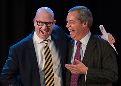 © Licensed to London News Pictures. 28/11/2016. London, UK. Nigel Farage (R) stands with Paul Nuttall onstage as he is announced as the new leader of the UK Independence Party (UKIP), at the Emmanuel Centre in Westminster London. Photo credit: Peter Macdiarmid/LNP