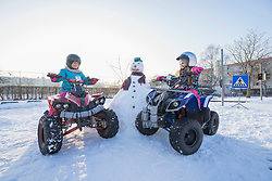 Girls riding quad bike on snow field