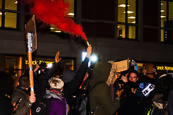 London, November 26th 2014. A vigil for teenager Mike Brown who was shot dead by a policeman in Ferguson, Missouri this year, takes place outside the US embassy in London. Anti-racism and human rights campaigners called the 'emergency' protest following a court verdict that clears Police Officer Darren Wilson of murder. PICTURED: Anti-police-racism marchers let off smoke bombs in London's exclusive Mayfair.