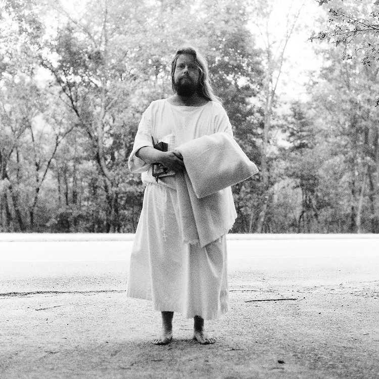 """BIRMINGHAM, AL – AUGUST, 2007: Carl James Joseph, a Catholic pilgrim from Detroit, Michigan, has been living without money and depending on the generosity of others since he began his pilgrimage in 1991. Known as """"The Jesus Guy,"""" he has visited 20 countries, and continues to walk barefoot across the United States, with only his robe, a blanket and hig Holy Bible."""