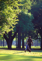 Stock photo of a man walking through the golf course with his supplies