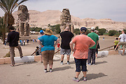 Large tourists visit the ancient Egyptian Colossi of Memnon site, Luxor Nile Valley, Egypt. The Colossi of Memnon (memorial temple of Amenophis III) are two massive stone statues of Pharaoh Amenhotep III, who reigned during Dynasty XVIII. For the past 3,400 years (since 1350 BC) they have stood in the Theban necropolis, west of the River Nile from the modern city of Luxor.