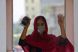 A woman walks through a disinfection tunnel after its installation during the nationwide lockdown to curb the spread of coronavirus (COVID-19) at Mirpur, in Dhaka, Bangladesh. Artoonad, a social organization of the youth, has set up a disinfection tunnel as the country struggles to contain the spread of the novel coronavirus. Photo by Suvra Kanti Das/ABACAPRESS.COM