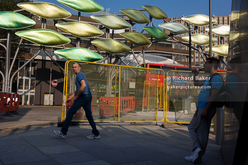 Commuters pass by Olympic street improvement works, beneath the new kinetic artwork called The Shoal.