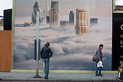 A man awaits a bus beneath a property developer's billboard showing a large aerial image of London skyscrapers in low cloud.