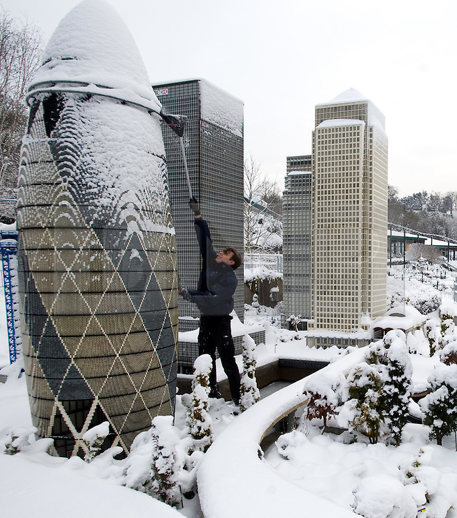 © under license to London News Pictures. 21/12/2010. A snow covered Lego London at Miniland, Legoland Windsor this morning (21/12/2010) following further snowfall last night. Pictured is model maker Joel brushing snow from the life like lego models of the UK capital. Photo credit should read: London News Pictures
