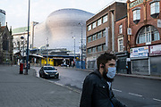 Man wearing a face mask passes near to the Selfridges building during the third national coronavirus lockdown in Birmingham city centre, which is deserted apart from a few people on 7th January 2021 in Birmingham, United Kingdom. Following the recent surge in cases including the new variant of Covid-19, this nationwide lockdown, which is an effective Tier Five, came into operation yesterday, with all citizens to follow the message to stay at home, protect the NHS and save lives.