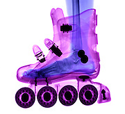 An X-ray of a Foot in a Rollerblade Boot. The rollerblade boot is shown in x-ray imaging.  The wheels and bearings are at the bottom and the latches and rivets appear as dark, since they are made out of denser materials.  This image is made from two different images.  The foot and rollerblade images were combined digitally due to the boot requiring a much larger x-ray exposure than the human foot.