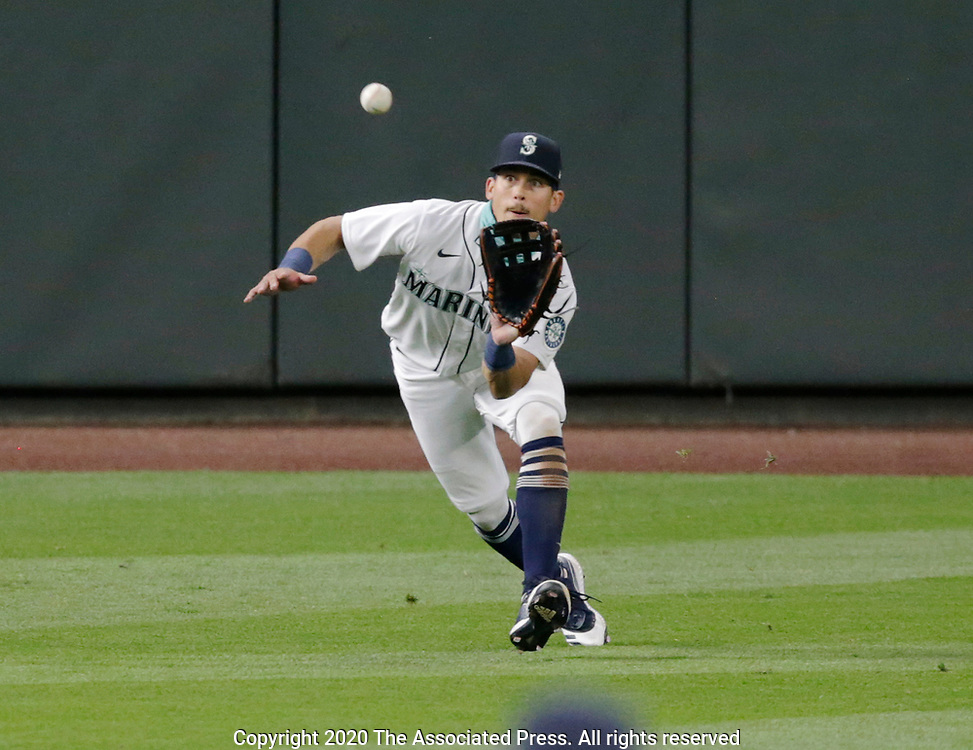 Seattle Mariners left fielder Sam Haggerty reaches to catch a fly ball for an out hit by Texas Rangers' Todd Frazier during the seventh inning of a baseball game, Saturday, Aug. 22, 2020, in Seattle. (AP Photo/John Froschauer)