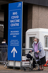© Licensed to London News Pictures. 18/01/2021. LONDON, UK.  A woman leaves a vaccination centre at the Olympic Office Centre in Wembley, north London.  This is one of ten new mass Covid vaccination centres opening today and they join the seven already in use across the country.  So far, 3.8 million people across the UK have received a first dose and the government hopes that number to rise to 15 million by 15 February.  Photo credit: Stephen Chung/LNP