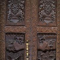 NEPAL, Kathmandu. Wood carvings of Buddha on temple door in Durbar Square.