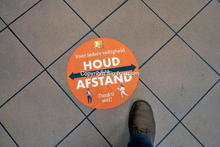 Nederland, Nijmegen, 24-7-2020 In een winkel, bakkerij, zijn stickers op de grond geplakt om de bezoekers te dwingen afstand van 1,5 ,anderhalve, meter te houden . Sticker, symbool,pictogram, associatie . Foto: Flip Franssen