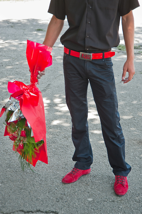 A young man brings flowers to his girlfriend at a university in Tashkent, Uzbekistan