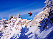 Freestyle alpine extreme skiier Dylan Crossman jumping rocky outcrop at Alta, Little Cottonwood Canyon, Utah.