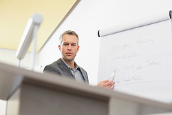Businessman at speaker desk with flip chart in auditorium