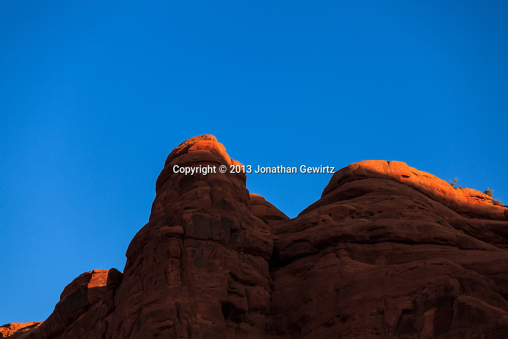 Morning sunlight outlines the tops of red rock cliffs in Arches National Park, Utah. WATERMARKS WILL NOT APPEAR ON PRINTS OR LICENSED IMAGES.