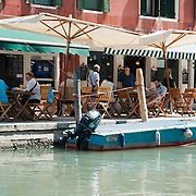"""VENICE, ITALY - JUNE 17: A local bacaro on the banks of a canal on June 17, 2011 in Venice, Italy. The bacari are the local down to earth version of wine bars, they serve  """"cicheti"""" a sort of Tapas, traditionally washed down with a glass of wine, and Venetians stop to snack and socialize before and after meals. ."""