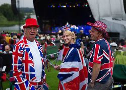 © Licensed to London News Pictures.22/08/15<br /> Castle Howard, North Yorkshire, UK. <br /> <br /> Friends wearing Union Flag clothing enjoy the evening as they and hundreds of other people attend the 25th anniversary of the Castle Howard Proms event near York. The theme of the event this year is a commemoration of the 75th anniversary of the Battle of Britain and the 70th anniversary of VE day and brings an evening of classic musical favourites celebrating Britishness to the lawns of Castle Howard.<br /> <br /> Photo credit : Ian Forsyth/LNP