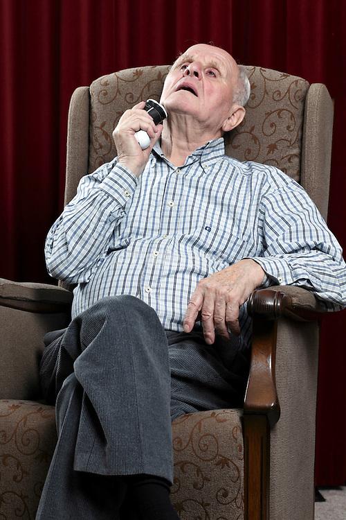 senior man shaving himself with an electric razor