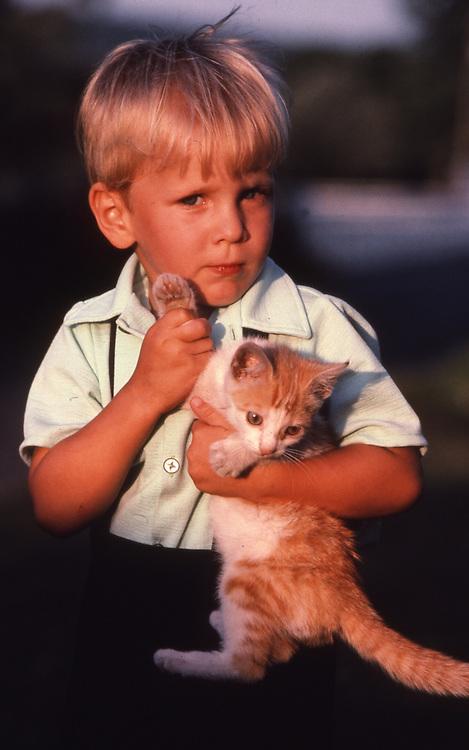 Amish child and cat, portrait on farm,  Lancaster, PA