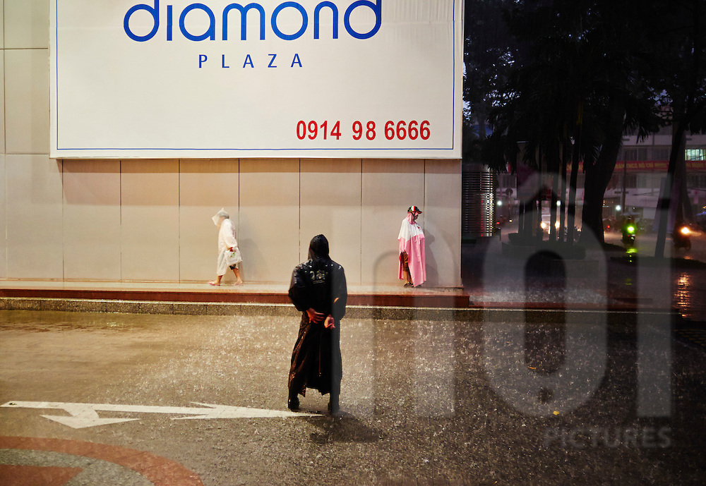 Three unrecognizable men stand at the parking lot entrance of Diamond Plaza during the heavy rains of a monsoon, Ho Chi Minh City, Vietnam, Southeast Asia